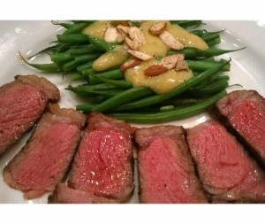 Here are four ounces of steak on a large dinner plate. Behind them are 12 ounces of green beans, with a mustard sauce.